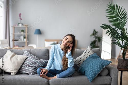 Fototapeta Attractive smiling woman talking on the phone at home. obraz na płótnie