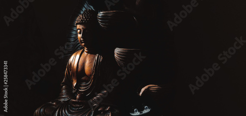 Pinturas sobre lienzo  Golden Gautama Buddha statue with a black background depicting darkness and hope coming in form of sunlight