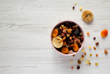 Dried Fruits And Nut Mix In A Pink Bowl On White Wooden Background, Top View. Overhead, From Above, Overhead. Copy Space.