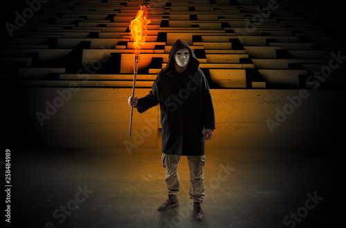 Ugly, aberrant man coming out from the labyrinth with burning flambeau on his ha Canvas Print