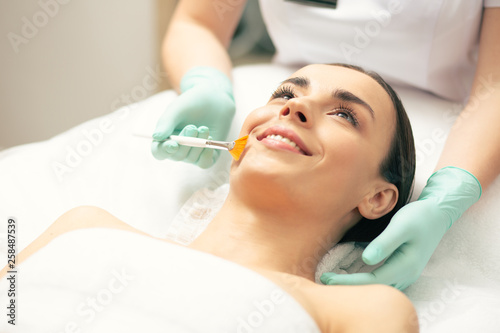 Fotomural  Young lady smiling while cosmetologist using peeling brush