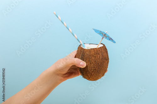 Fotografia  Tropical cocktail in coconut with straw and an umbrella in hand of girl on blue background