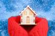 Hands in knitted mittens Holding model House on winter background. House Energy Efficiency Concept. Warm home.