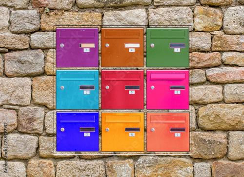 Fototapeta Boîtes aux lettres couleurs incrustées dans mur de pierres