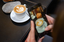 Female Food Blogger Taking A Cappuccino Shot With Her Smartphone On A Restaurant Table