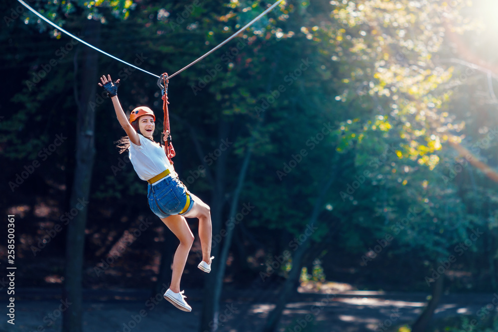 Fototapeta Happy women girl female gliding climbing in extreme road trolley zipline in forest on carabiner safety link on tree to tree top rope adventure park. Family weekend children kids activities concept