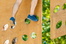 Male Legs In Sneakers Keep Balance On Wooden Boards With Round Slits Hanging On Ropes On High Trees In Park. Rope Park With Different Obstacles And Ziplines. Extreme Rest And Summer Activities Concept