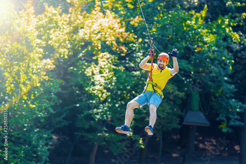 Fotografía  Happy men boy male gliding climbing down in extreme road trolley zipline in forest on carabiner safety link on tree to tree top rope adventure park