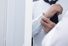 Man Tying The Cuffes In Front Of Mirror