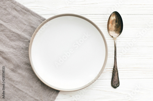 Stylish empty plate with vintage spoon on napkin on white table, flat lay. Modern set, serving for reception and celebration. Party and diet concept. Copy space
