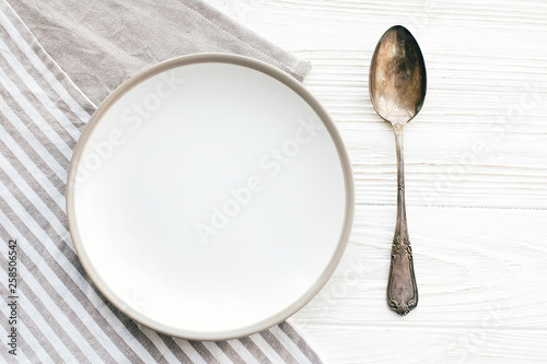 Diet concept. Stylish empty plate with vintage spoon on napkin on white table, flat lay. Modern set, serving for reception and party celebration. Copy space