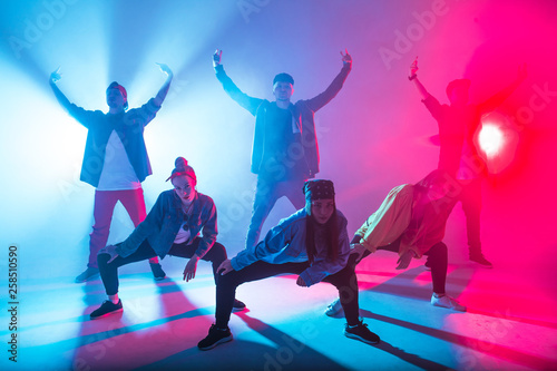 Keuken foto achterwand Dance School Young modern dancing group of six adult young people practice dancing on colorful background