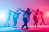 Young modern dancing group of six adult young people practice dancing on colorful background. Fashionably dressed youngsters moving over blurred disco club color lights