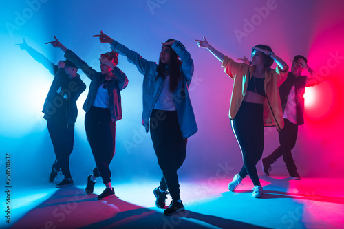 Fototapety Taniec  animation-group-of-young-women-and-men-dancing-over-red-and-blue-dual-color-light-on-dark
