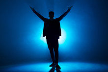 Full-size Of Silhouette Of Male Break Dancer Performing On Blue Neon Stage His Expressive Dance, Dark Blue Background With Light Flare On Background