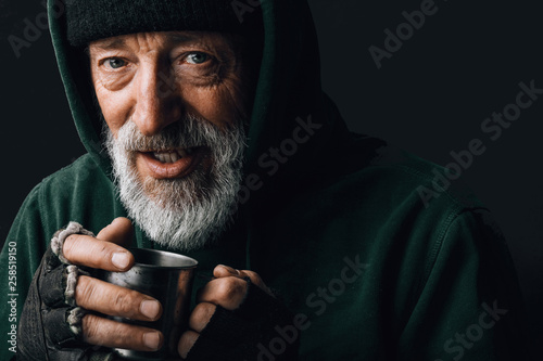 Photo Frozen homeless bearded old man with grey hair and wrinkled face, looks at camer