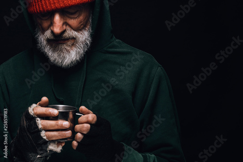 Photo Old homeless man with grey beard covering up in green decrepit wear holding a mu