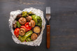 Baked vegetables in foil - tomatoes, eggplants, peppers on a gray wooden table. Copy space. Top view
