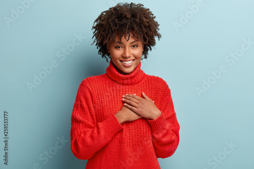 Photo of emotional dark skinned female touches heart with both palms, demonstrat Canvas Print