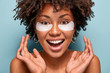 Leinwandbild Motiv Headshot of ovejoyed beautiful woman reduces under eye puffiness, dark circles, applies moisturizing patches, cares of eye skin beauty, smiles broadly, wants to touch soft face, isolated on blue