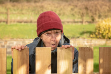 Shocked Mature Woman Looking Over Fence