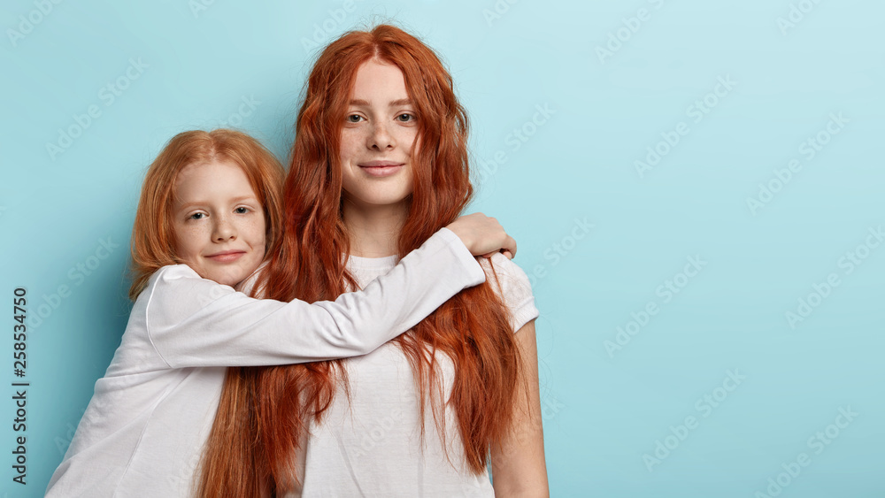 Fototapety, obrazy: Two adorable foxy girls sisters embrace indoor, look at camera with green eyes. Pretty freckled little child embraces with love best friend, have friendly relationships. I am always by your side