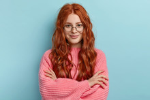 Satisfied Ginger Charming Woman With Curly Hair, Wears Transparent Glasses, Keeps Arms Folded Over Chest, Has Pleasant Talk With Contemporary, Wears Oversized Clothes, Isolated Over Blue Background