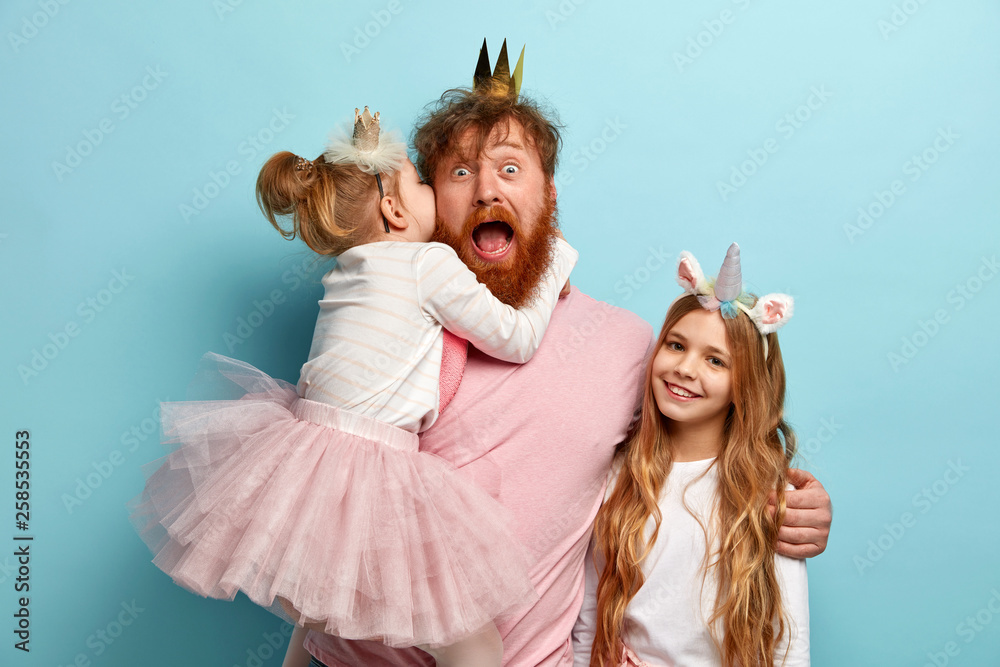 Fototapeta Mad father hears secret from daughter, spends free time with children, embraces and shares love, wear carnival costumes for party, isolated over blue wall. Kids and parents concept. Festive event