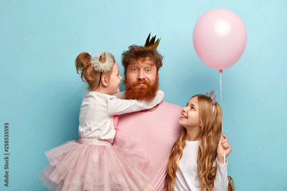 Fototapeta Busy father organizes holiday on International childrens day for two daughters, have home party, wear crowns and festive clothes. Little adorable girl holds air balloon, looks at dad and sister