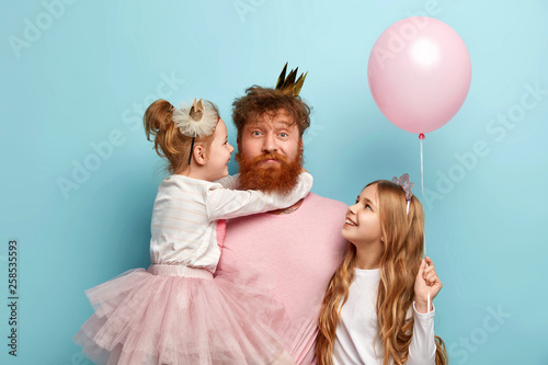 Obraz Busy father organizes holiday on International childrens day for two daughters, have home party, wear crowns and festive clothes. Little adorable girl holds air balloon, looks at dad and sister - fototapety do salonu
