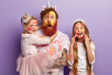 Emotional Father With Thick Ginger Beard, Carries Small Child On Hands, Spends Spare Time With Two Daughters, Have Dirty Faces With Oil Paints, Draw Picture, Prepare For Party, Isolated On Purple Wall