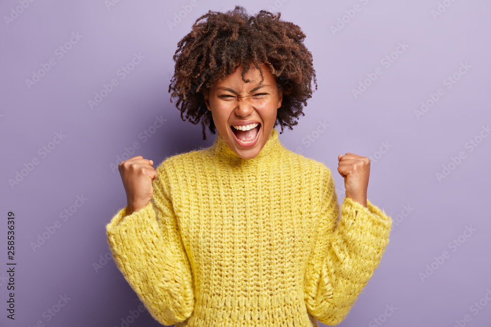 Fototapeta Horizontal shot of overjoyed glad woman with curly hair, clenches fists like winner, exclaims positively, sure in success, celebrates achieved success, wears yellow winter jumper, feels pleasure