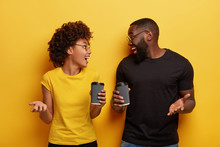 Afro Couple Feel Excited, Hold Paper Cups Of Coffee, Laugh And Gesture With Hands, Wear Spectacles, Have Fun Together While Drink Hot Beverage, Isolated Over Yellow Background. Coffee Culture