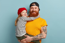 Isolated Shot Of Happy Father With Ginger Beard, Yellow T Shirt, Carries Small Daughter, Recieves Hug With Love, Spend Free Time Together In Family Circle, Express Positive Emotions. Parents, Children