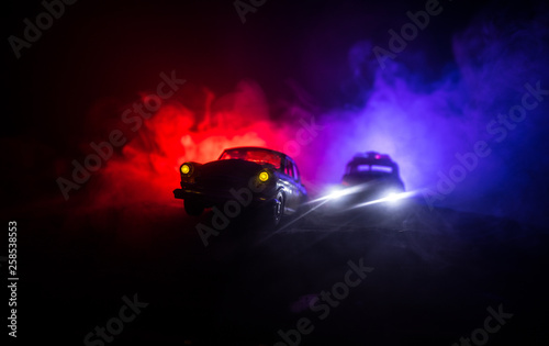 Fototapeta Police car chasing a car at night with fog background