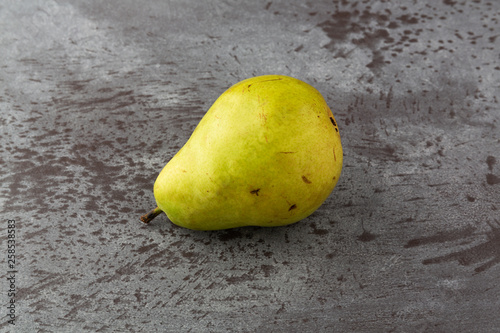 Single green anjou pear on a gray mottled background side view Canvas Print