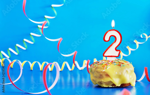 Fototapeta Birthday of two years. Cupcake with white burning candle in the form of number 2. Vivid blue background with copy space obraz