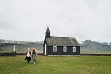 A Couple Is Near A Black Wooden Church In Iceland. Budir Church.