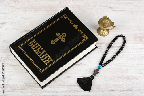 Holy Bible, rosary beads with cross and incense burner on white wooden background. Religion concept and faith. Cyrillic text means Bible in bulgarian and russian