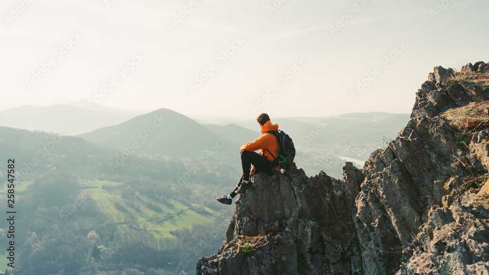 Fototapety, obrazy:  Young man with backpack sitting on rock looking into the landscape. Listening to the silence. Beautiful moment the miracle of nature.