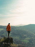 Adventurous Man Enjoying the Miracle of Nature. Man hike with red jacket. Travel concept. Photographer looks into the landscape and listen the silence