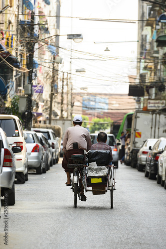 Photo A unidentified Sai Kaa driver is carrying a passenger on his side car among the narrow streets of Yangon, Myanmar