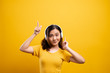 Leinwanddruck Bild - Woman with headphones listening music on isolated yellow background