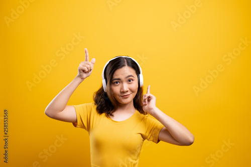 Woman with headphones listening music on isolated yellow background - 258553569