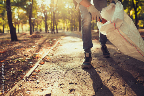 Fotomural young man picking up trash outdoor. close up