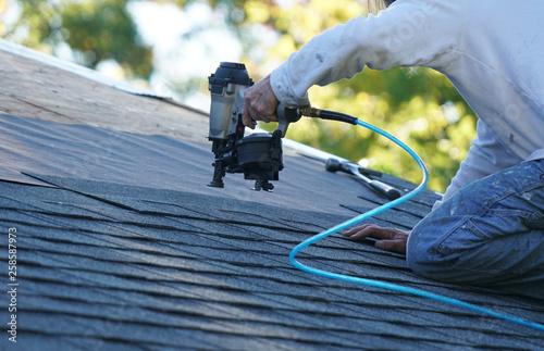 Cuadros en Lienzo  handyman using nail gun to install shingle to repair roof