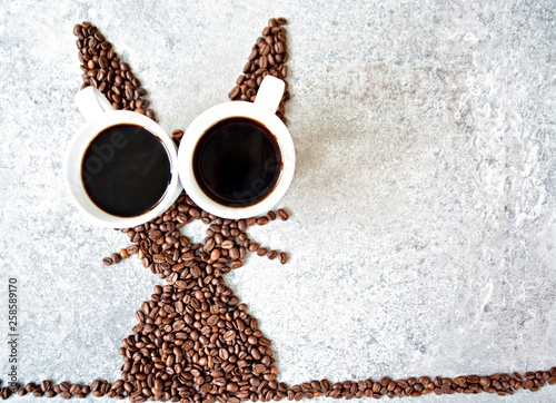 Fotobehang Cafe With fresh coffee beans and two cups of freshly brewed black coffee, a hare is shaped on a bright marble surface - concept with coffee beans as a gift for Easter - with room for text or other elements