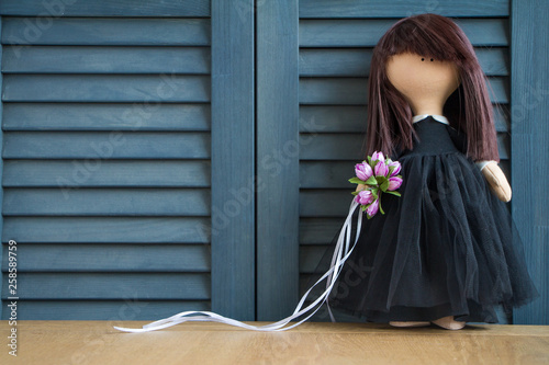 Fotografía Tilda doll with black hair and a bouquet of purple flowers