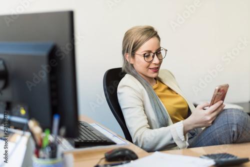 Fototapeta Young woman looking smartphone at work in a break obraz