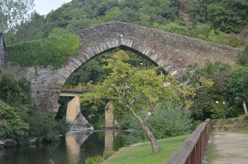 Fototapeta na wymiar Wonderful Medieval Style Bridge Crossing The Suarna River On Its Pass By Navia De Suarna. Nature, Architecture, History, Street Photography. August 23, 2014. Navia De Suarna, Lugo, Galicia, Spain.